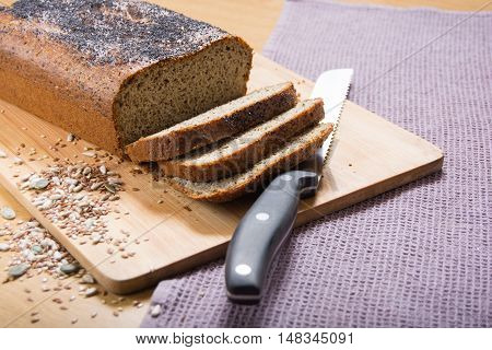 Freshly baked sliced banting seed loaf or paleo bread on a board with bread knife and seeds poster