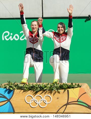 RIO DE JANEIRO, BRAZIL - AUGUST 14, 2016: Olympic champions team Russia Ekaterina Makarova (L) and Elena Vesnina during medal ceremony after tennis women's doubles final of the Rio 2016 Olympic Games
