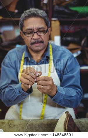 Shoemaker putting thread in the needle in workshop