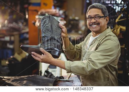 Portrait of smiling shoemaker holding a leather boot in workshop