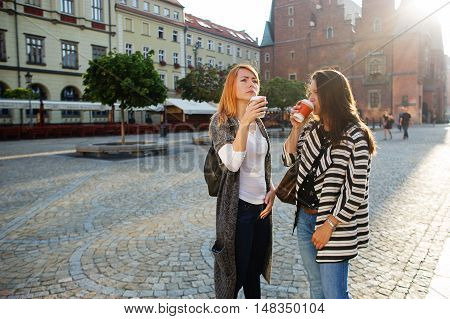 Two cute girlfriends stood in the empty cozy square European city. Girls have coffee from disposable glasses and admire a city architecture. Walk it gives pleasure.