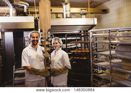 Portrait of female and male baker standing together in bakery shop