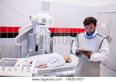 Doctor using digital tablet and patient lying on x ray machine in hospital