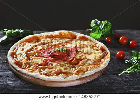 Delicious fresh margharita Pizza on the wooden background. Top view.