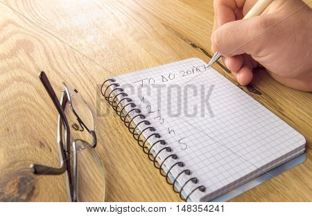 2017 to do list concept - Man's hand writing the to do list for 2017 on a graph spiral notebook placed on a wooden table with eyeglasses besides.