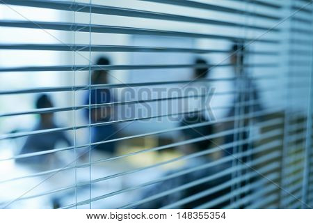 Business people having meeting, view through blinds