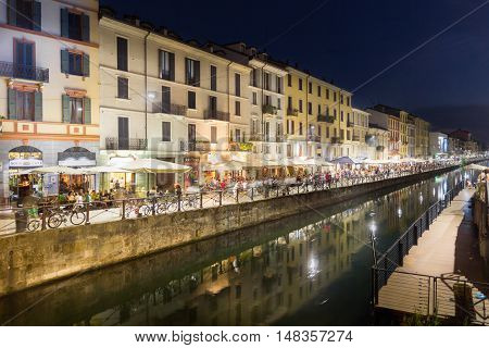 MILAN, ITALY - AUGUST 14, 2016: Tourists walking in by the Naviglio Grande canal in the Navigli district. The area is famous by its five canals and the lively nightlife.