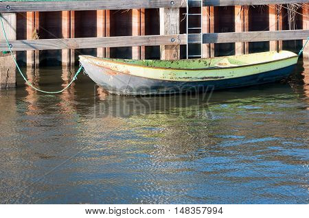 Old rusting steel rowboat with a green rope moored to a hardwood quay of a small lake on a sunny day in the summer season.