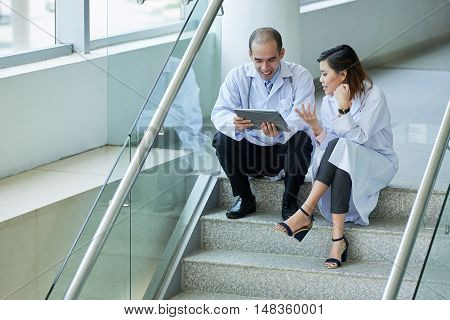 Young colleagues sitting on stairs and discussing case history