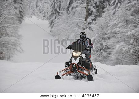 young man posing on snowmobile at beautiful winter day