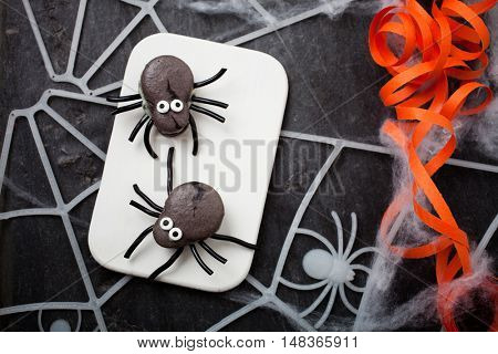 Dark grey spider macaroons with licorice