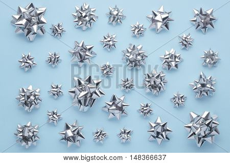 Set of silver bows on blue. Holiday's ribbon bows for decoration gifts