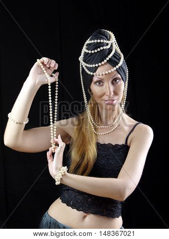 beautiful young blonde woman with long hair and a pearl dances an oriental dance on dark background