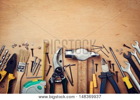 Working tools on wooden rustic background, top view.
