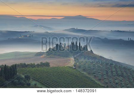 Tuscany. Image of Tuscany landscape during foggy autumn sunrise.