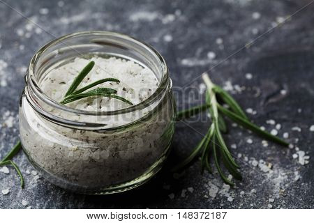 Sea salt scented herb rosemary on black stone background, vintage style.