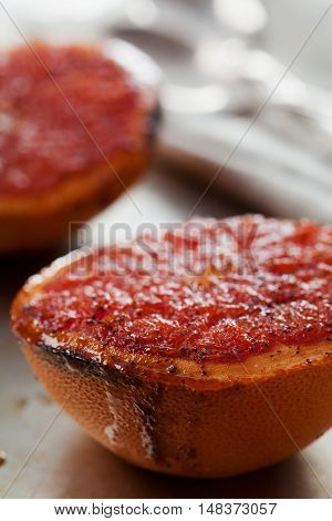 Vintage image of broiled grapefruit with brown sugar and cinnamon on metal surface. Healthy dessert is good for breakfast or snacks. Macro.