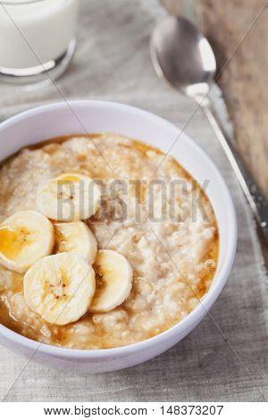 Bowl of oatmeal porridge with banana and caramel sauce on rustic table. Hot and healthy breakfast, diet food.