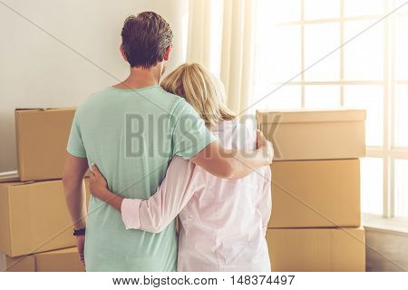 Back view of beautiful mature couple in casual clothes hugging and looking at packed boxes while moving to the new apartment