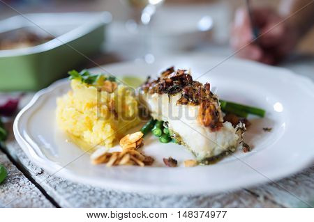 Zander fish fillet dish on a plate on a white wooden table