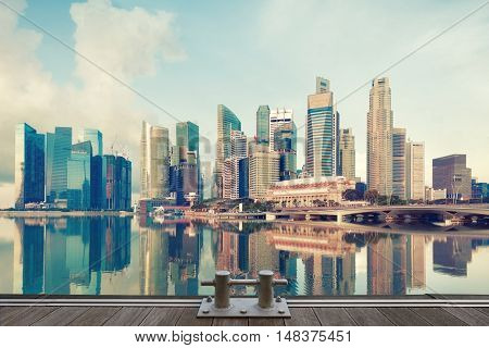 Singapore central quay with wooden pier and bollard on foreground. Modern city architecture at sunrise.