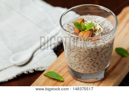 Chia seeds pudding or smoothie with oat banana and almonds, decorated with mint leaves. Vegetarian superfood.
