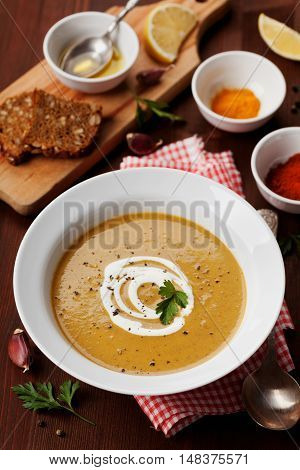 Lentil cream soup in a bowl with spices turmeric, paprika and garlic on wooden table.