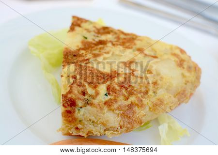 Spanish omelette served on a white plate