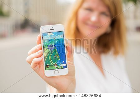 RIGA LATVIA - July 14 2016: Woman showing sample screenshot of Pokemon Go on the phone. Pokemon Go is a location-based augmented reality mobile game.