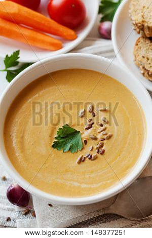 Vegetarian vegetable cream soup with eggplant and carrots in white bowl on wooden table, selective focus. Top view.