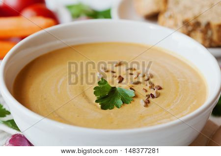 Vegetarian vegetable cream soup with eggplant and carrots in white bowl on wooden table, selective focus.