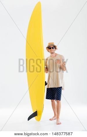 Smiling young curly surfer showing shaka or hang loose sign gesture and holding surfboard isolated on the white background