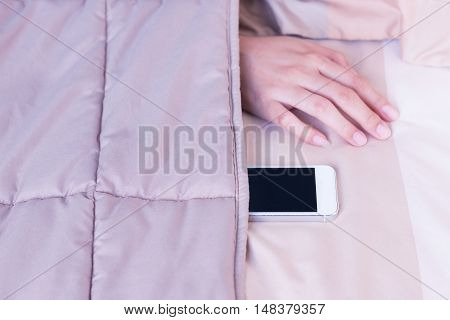 Woman hand under blanket being woken by mobile phone in bedroom.