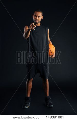 Concentrated serious african sports man holding basket ball and pointing finger at camera isolated on a black background