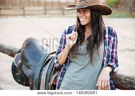 Happy smiling cowgirl in hat holding straw in mouth while leaning on the ranch fence