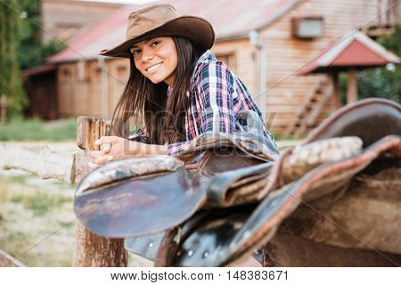 Smiling brunette young woman cowgirl leaning on fence in village and looking at camera