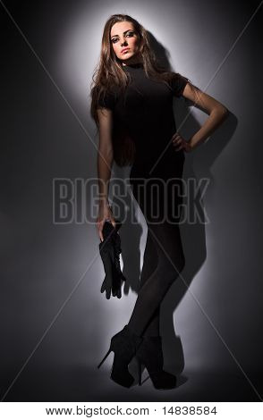 Young Slim Glamour Lady With Long Hairs Dressed In Black Combi Dress, Dark Key Studio Portrait