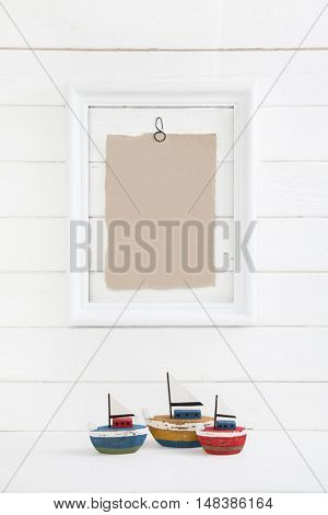 Three sail boast on a white wooden background with a picture frame in mock up style empty and nobody for concepts.