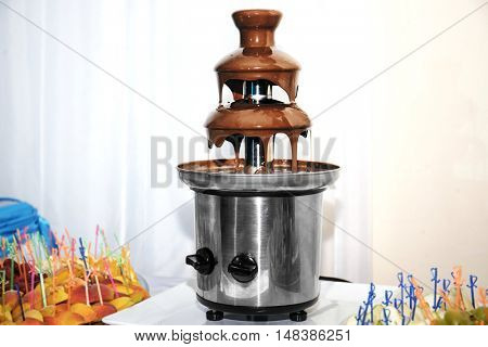 Chocolate fondue fountain and fruit on a table