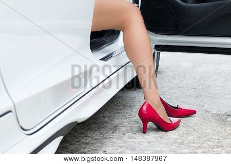 Leg of sexy woman wearing red high heels sitting in a car.