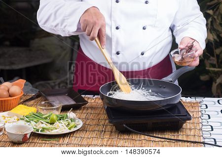 Chef stir fried rice noodle for cooking Pad Thai / cooking Pad Thai concept