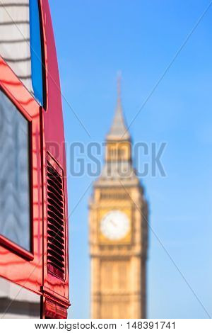 Side detail of red London bus with reflections at the windows, paint and advertising space, Big Ben clock tower in the distance (copy space)