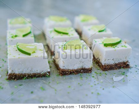 Raw vegan lime coconut cheesecake on marble table, background. Selective focus. Toning. Close-up.