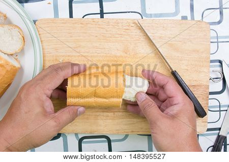 Hand with knife penetrate bread / cooking sausage bread concept