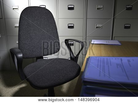 a single office chair in empty office with filing cabinets