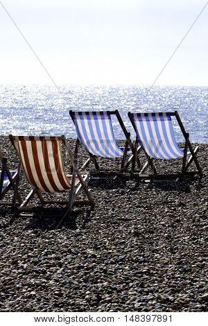 a group of empty deckchairs on a pebbly beach looking out to sea
