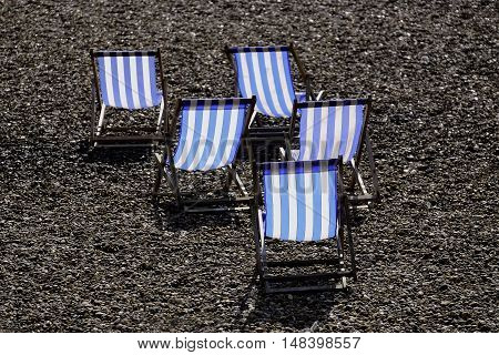 Five blue and white striped empty deckchairs on a pebbly beack