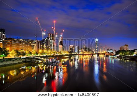 View of London at night from Lambeth Bridge showing St Georges Wharf and St Georges Tower cranes and River Thames