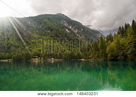 Lago di Fusine (Fusine Lake). Small mountain lake with forest and green water. Julian Alps Tarvisio Friuli Venezia Giulia Italy poster