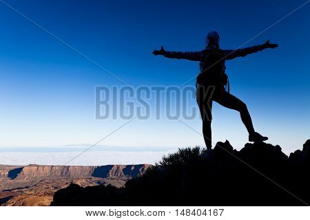 Woman successful hiking climbing silhouette in mountains motivation and inspiration landscape on island and ocean. Hiker arms up outstretched on mountain top looking at view on Tenerfie Spain.